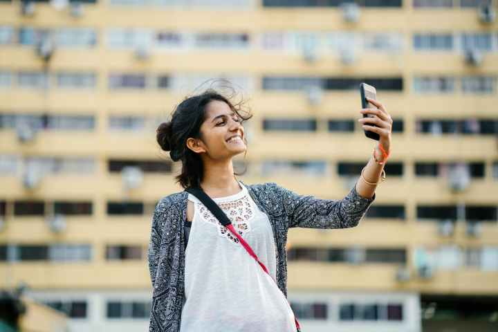 smiling woman holding black smartphone