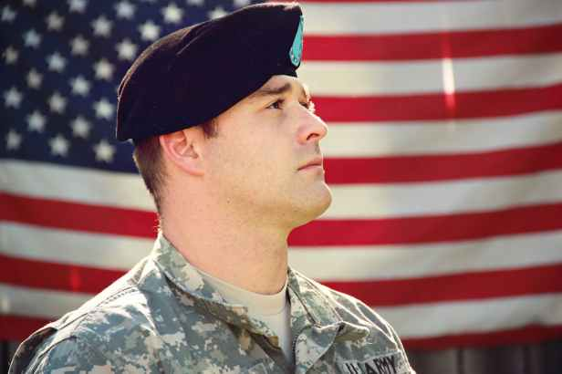 man wearing combat hat and top looking up near flag of america