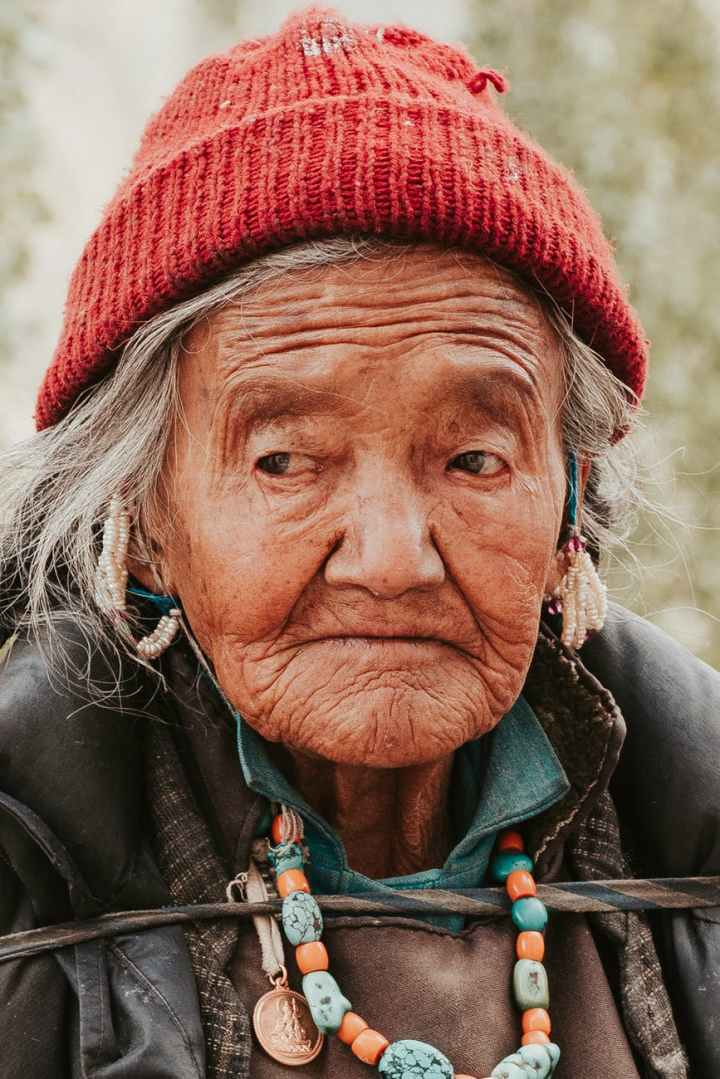 close up photo of an old woman wearing red knit cap