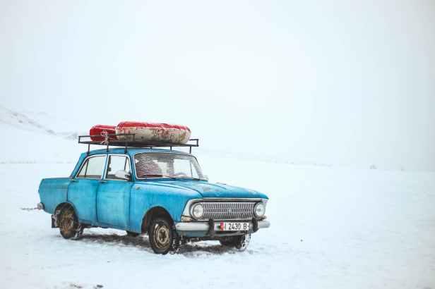 blue sedan on snow at daytime