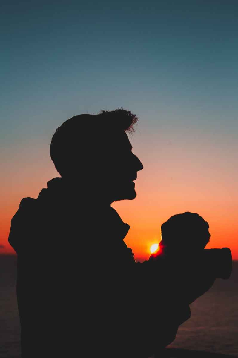 silhouette photography of man holding baby
