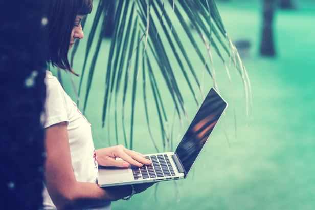 woman in white t shirt using macbook pro