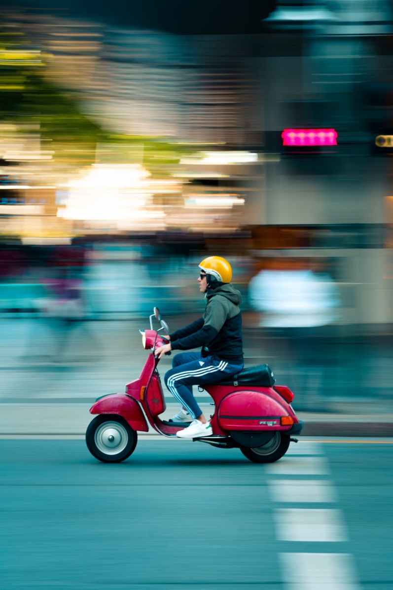 photo of man riding red motor scooter