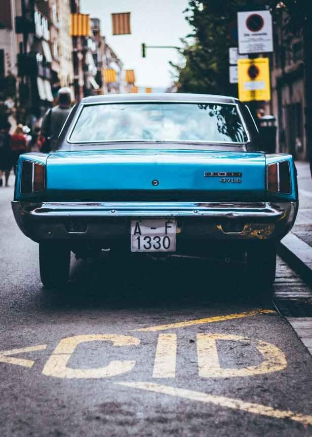 close up photo of blue vehicle on street