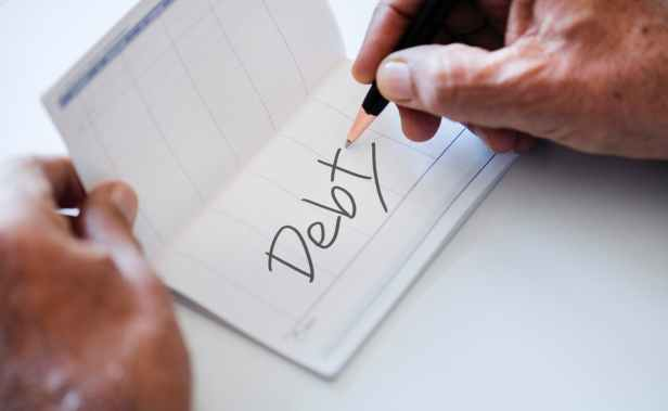 person writing debt on paper