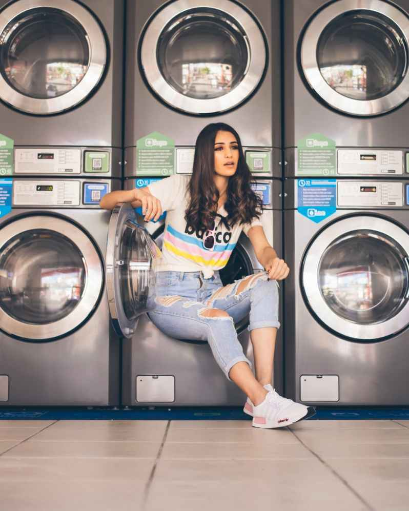 woman in jeans sitting on washer