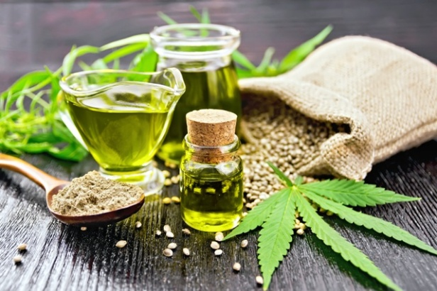 Oil hemp in two jars and sauceboat on wooden board